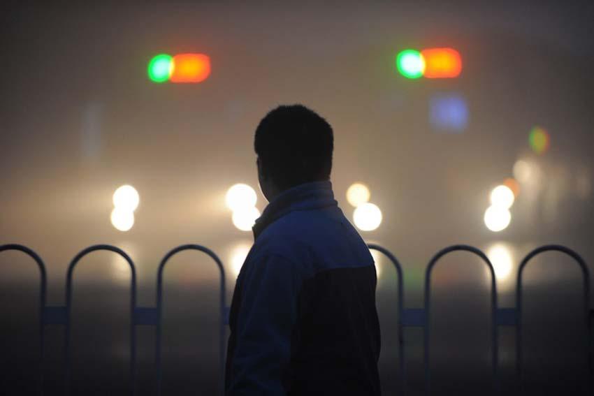 12月7日,一名男子走在雾霾迷漫的安徽合肥街头。