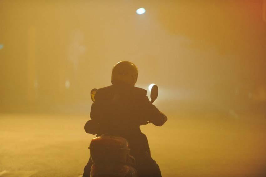 12月7日,市民在雾霾迷漫安徽合肥街头骑行。