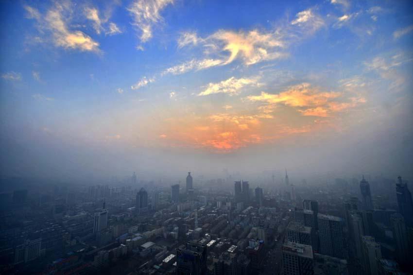 12月7日,山东济南,300米高空俯瞰泉城,地面笼罩着一层灰色的雾霾带。