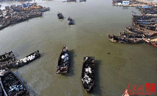 几艘满载油桶的渔船在
